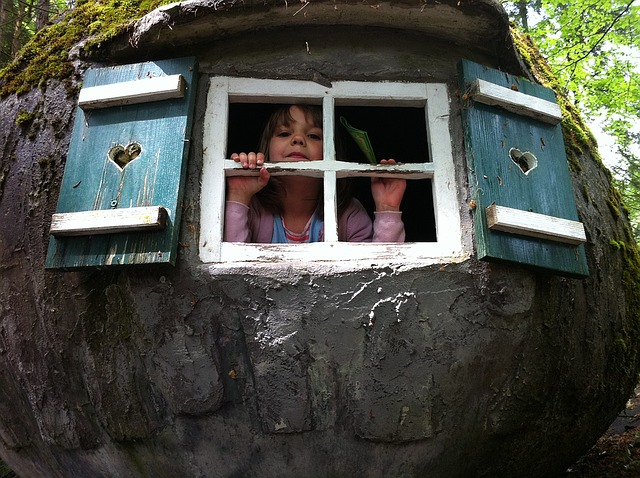 Young girl looking out window of tree house