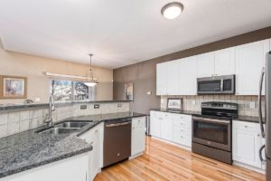 Columbus OH Kitchen with grey granite counters, fresh white cabinets, stainless steel appliances, and hardwood floors.