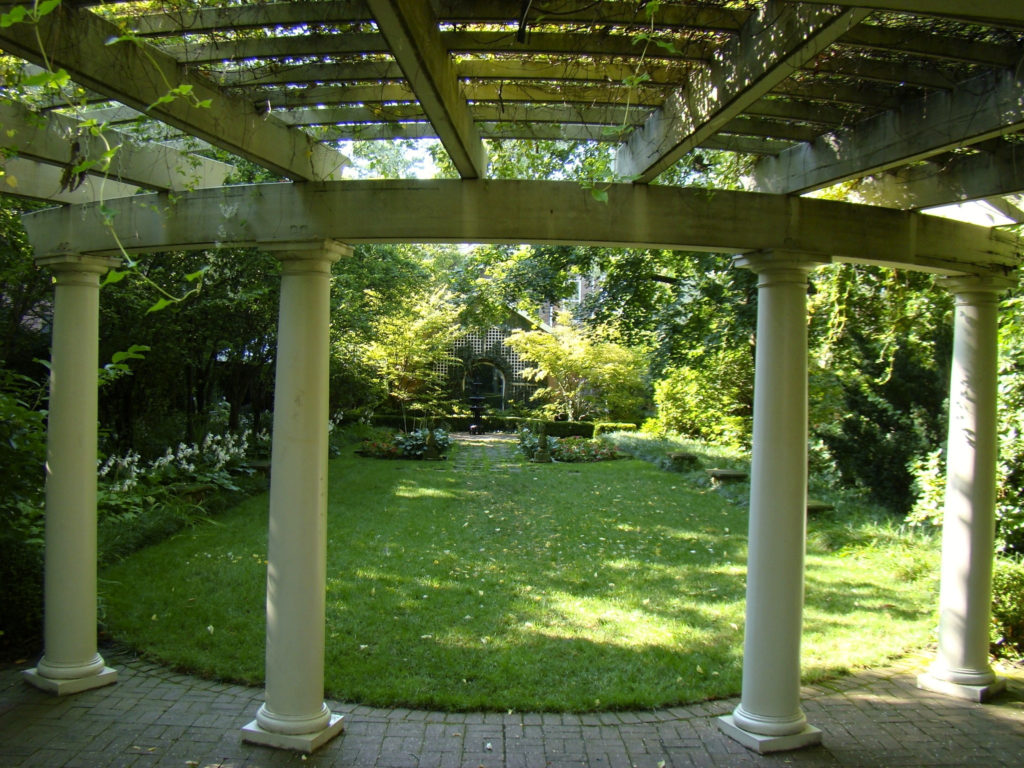 Trellis or pergola with columns looking out of garden at Kelton House