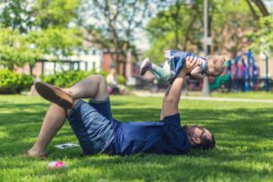 Dad laying in grass holding up toddler