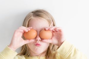 girl holding eggs over eyes