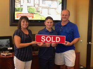 Westerville family holding a Sold sign and standing in front of home sold by Realtor Rita Boswell